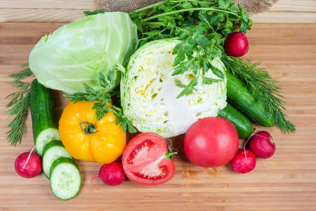 Different fresh washed vegetables and greens close-up on a wooden bamboo cutting board, top view Banque d'images - 124065499