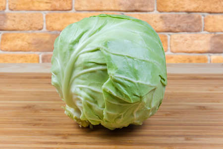 Whole head of the young white cabbage on the wooden bamboo cutting board Banque d'images - 124066920