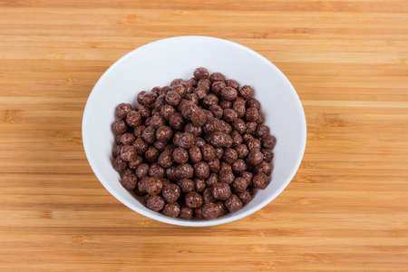 Breakfast cereal chocolate balls in white bowl on a wooden bamboo surface Stock Photo