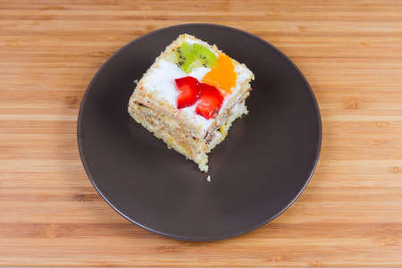 Slice of the layered sponge cake with cream coating and fresh fruits and berry slices decoration on the brown dish on wooden surface