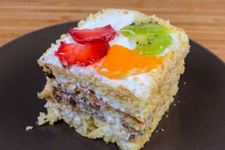 Slice of the layered sponge cake with cream coating and decoration with slices of fresh fruits and berry on the brown dish, fragment close-up in selective focus 免版税图像
