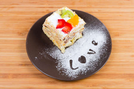 Piece of the layered sponge cake with cream coating and decoration of slices fresh fruits and berry on the brown dish on a wooden surface