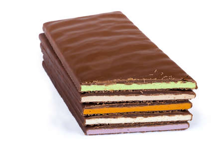 Stack of several blocks of the milk chocolate with filling different colors, cut at an angle on a white background