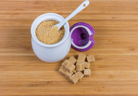 Natural unrefined brown granulated sugar in white sugar-bowl with spoon and cubes of brown sugar scattered beside to her on a wooden surface Standard-Bild