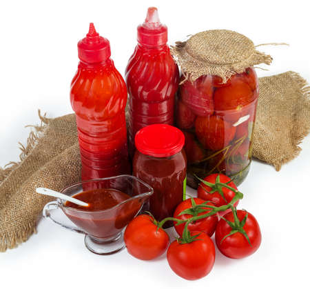 Various tomato sauces in plastic bottles, glass jar, glass gravy boat, fresh and canned tomatoes on a white background