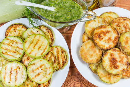 Grilled and fried in batter vegetable marrows sliced by circles in two dishes and garlic sauce in sauce boat. Fragment close-up, top view Imagens