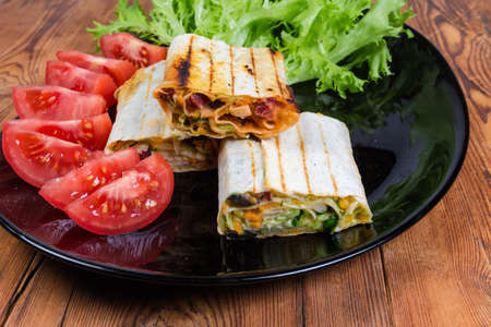 Grilled pieces of wrapped flatbreads stuffed with salad of chopped meat, vegetable and sauce on the black dish with lettuce and tomatoes on the old rustic table, fragment close-up