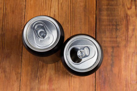 One open and one closed modern black beverage cans made of aluminum alloy on the rustic table, top view close-up in selective focus Фото со стока