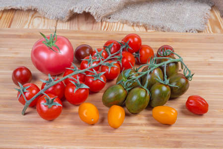 Different varicolored fresh ripe cherry tomatoes and ordinary pink tomato on the wooden cutting board