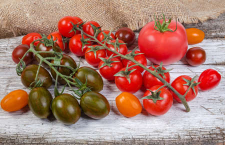 Different varicolored fresh ripe cherry tomatoes and single ordinary pink tomato on the old cracked wooden surface with burlap