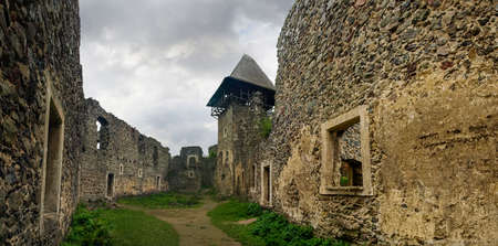Picturesque ruins of the part of courtyard and main tower-donjon of the ancient stone Nevytske Castle of the 13-17th centuries, Zakarpattia Oblast, Ukraine Stock Photo