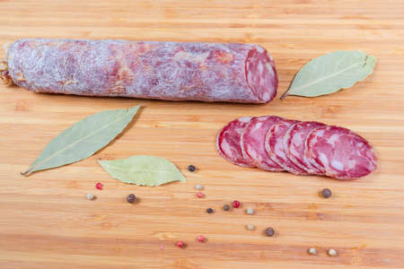Partly sliced dry-cured sausage among some spices on the wooden cutting board Zdjęcie Seryjne