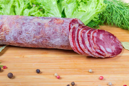 Partly sliced dry-cured sausage among some spices on the wooden cutting board on background of greens, close-up in selective focus