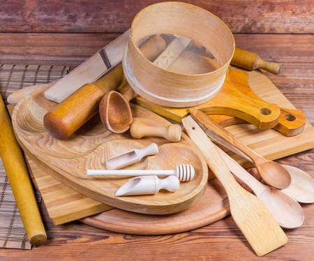 Pile of various kitchen utensils made from different natural wood type on the rustic table Foto de archivo