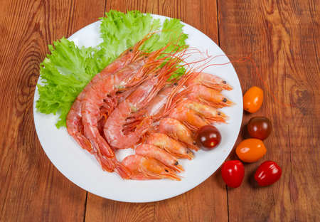 Argentinian red shrimps and usual shrimps with fresh lettuce leaves on dish and varicolored tomatoes cherry on the wooden rustic table