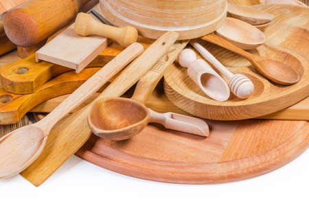 Pile of various kitchen utensils made from different natural wood type close-up in selective focus on a white background
