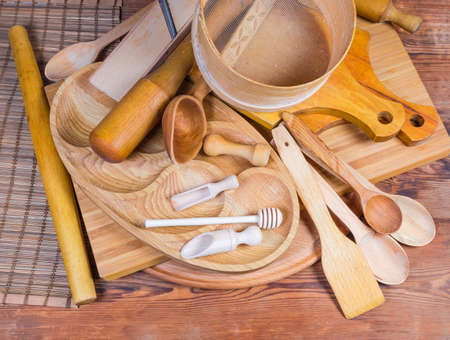 Pile of various kitchen utensils made from different natural wood type on the rustic table, top view Foto de archivo