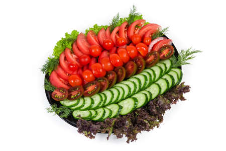 Vegetable salad with fresh sliced various tomatoes and cucumbers on green and red lettuce leaves on the black dish on a white background
