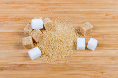 Small pile of the natural unrefined brown sugar and cubes of brown and white sugar on a bamboo wooden surface close-up