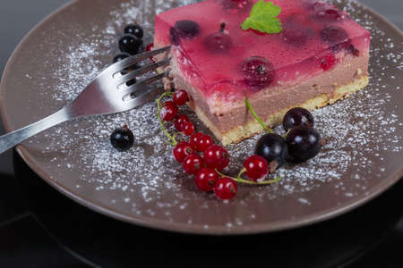 Piece of the layered cake with jelly coating and fresh red and black currant berries on brown dish with fork on dark surface, fragment close-up in selective focus