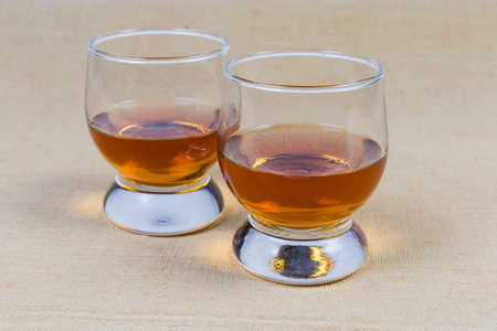 Two portions of brandy in brandy bowls on tablecloth closeup