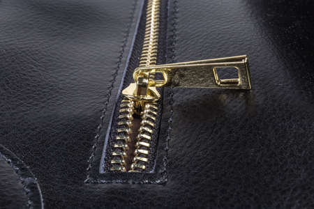 Fragment of the partly unbuttoned yellow metal zipper with slider of the black leather women's handbag close-up in selective focus