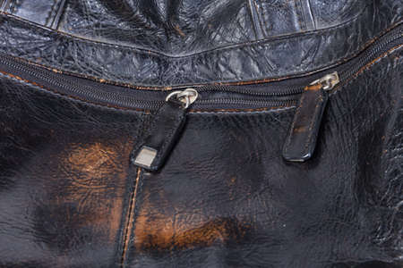 Fragment of partly unbuttoned zipper with two sliders with leather pullers on the old shabby black leather mens handbag Imagens