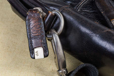 Fragment of the old shabby black men's leather handbag with bag accessories - zipper with leather puller and letters VIP on metal insert on him, swivel snap hook of the shoulder strap close-up Standard-Bild