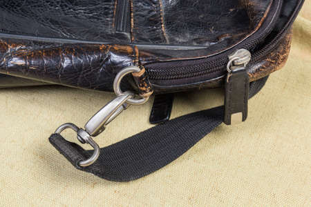 Fragment of the old shabby black men's leather handbag with bag accessories - zipper with leather puller and swivel snap hook of the shoulder strap Stock fotó