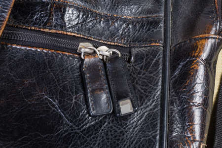 Fragment of the old shabby black mens handbag and plastic zipper with two sliders with leather pullers Imagens