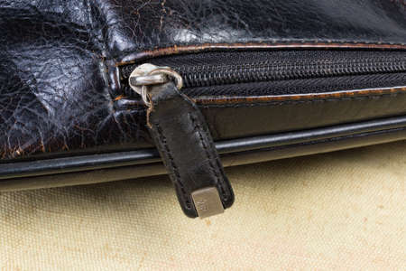 Fragment of the old the shabby black men's handbag and zipper with slider with leather puller and letters VIP on metal insert on him