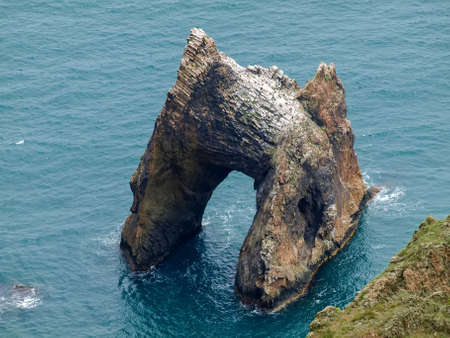 Scenic rock arch of volcanic origin in water near the sea shore on a background of the water, view from the high bank Imagens