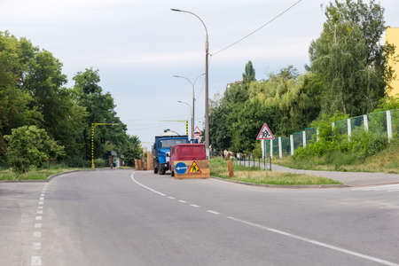 Fragment of town street with fenced section, marked with road signs during of a road repair in summer