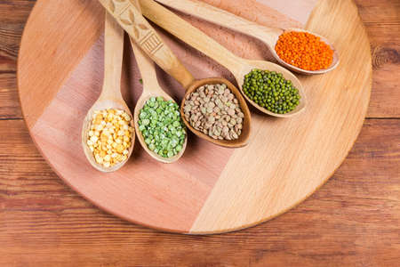 Various raw legumes - yellow and green split peas, red and brown lentils and mung beans in the wooden spoons on serving board on the old rustic table, top view