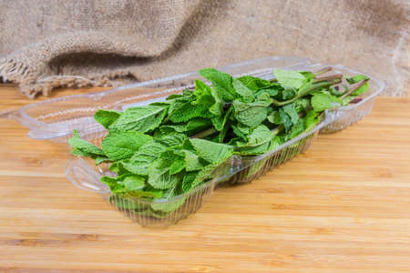 Fresh spearmint in open transparent plastic container on a wooden surface close-up in selective focus