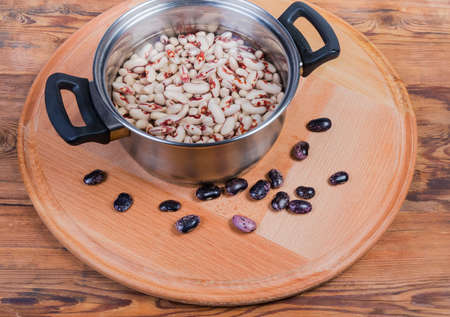 Uncooked soaked speckled red with white kidney beans in stainless steel cooking pot with water and dry purple beans beside on the wooden service board