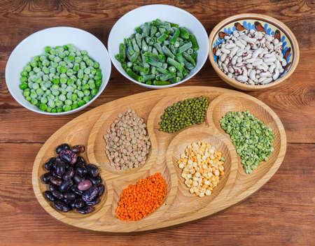 Raw legumes - varicolored dried split peas and frozen green peas, purple and white-red kidney beans and frozen green beans, lentils and mung beans in various dishes on the old rustic table