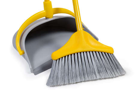 Kit of the yellow plastic broom with gray bristles for sweeping floors and dustpan on a white background, working parts close-up Imagens