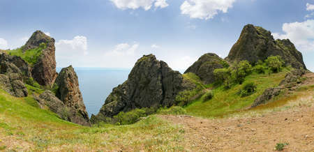 Rocky ridge with outcrops volcanic origin above the sea, panoramic view in the direction of the sea side Imagens