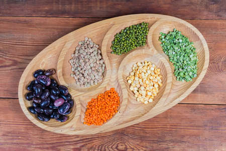Raw legumes - different split peas, purple kidney beans, different lentils and mung beans on the wooden serving dish on the old rustic table, top view Imagens