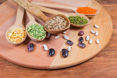 Various raw legumes - yellow and green split peas, red and brown lentils, mung beans in the wooden spoons and different kidney beans scattered beside to them on wooden surface