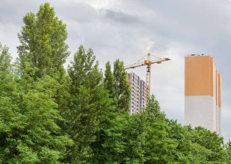 Multi story residential houses during construction with building tower crane and trees on the foreground against of the cloudy sky