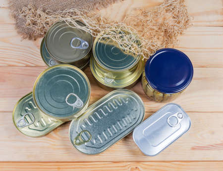Various types of sealed tin cans and glass jar of canned fish and seafoods on the rustic table, top view 写真素材