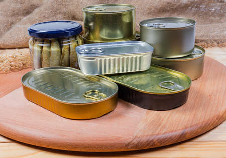 Set of canned fish and seafoods in various types of sealed tin cans and glass jar on the wooden service board