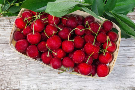 Ripe red sweet cherries with stalks in small wooden basket and cherry leaves on the old wooden cracked surface, top view
