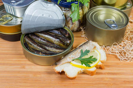 Smoked sprats in cooking oil in the open tin can, open sandwich with sprat and lemon against of other canned fish close-up Stock Photo