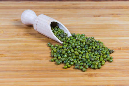 Ripe whole mung beans in wooden spice spoon and scattered beside her on a bamboo wooden surface close-up in selective focus