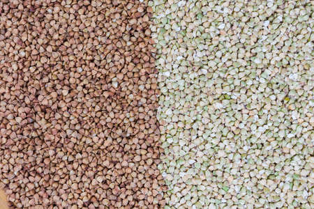 Background of two types of the uncooked wholegrain buckwheat groats - green not steamed and brown pre-steamed, top view Banco de Imagens
