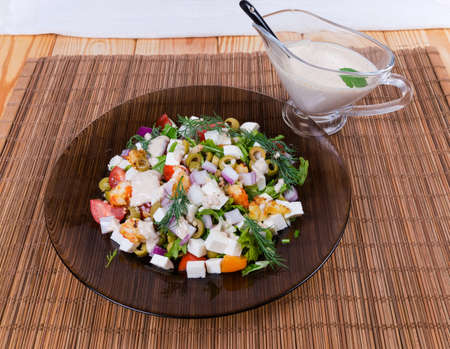 Vegetable salad of cherry tomatoes, olives, sliced onion, greens, rennet soft cheese, fried shrimps on glass dish, white sauce in sauce boat on the bamboo table mat