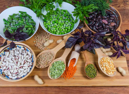 Various raw dried and frozen legumes in diffetent dishes and wooden spoons on the wooden cutting board on the rustic table Фото со стока
